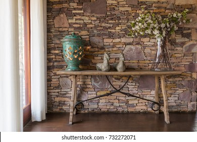 Living room with decorative table, stone wall behind.