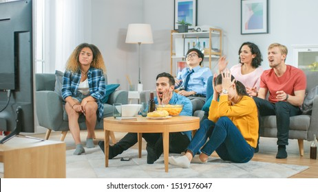 In the Living Room Diverse Group of Friends on Watching Sports Game Match on TV, They Cheer and Chant for the Team, But are Disappointed after Team Loses. Cozy Room with Snacks and Drinks