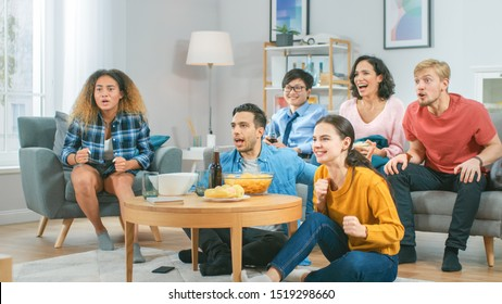 In the Living Room Diverse Group of Friends on Watching Sports Game Match on TV, They Cheer and Chant for the Team, Celebrate Victory after Team Scoring Winning Goal. Cozy Room with Snacks and Drinks