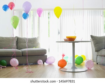 Living room full of colorful balloons by sofa