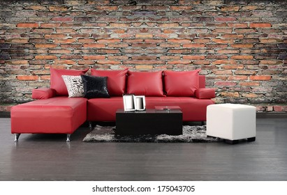 Living room. Furniture on hardwood floor against rough brick wall.