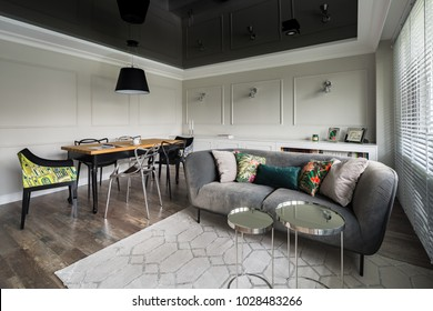 Living room with gray couch and wooden dining table and black stretch ceiling