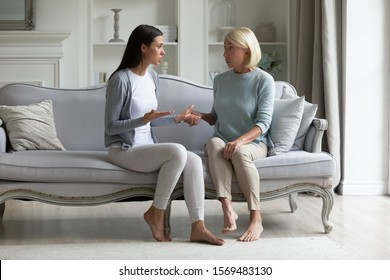 In living room grown up daughter sitting on couch with elderly mother proves her right. Different generation women having dispute, concept of generational gap, misunderstanding, difference of opinion