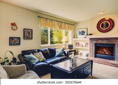 Living room interior with brick background fireplace, leather furniture set and black coffee table with drawers