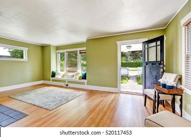 Living room interior of craftsman home with open entrance door, window seat with pillows, pale green walls and hardwood floor. Northwest, USA