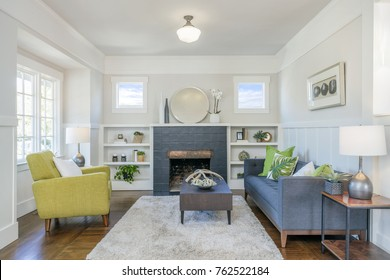 Living room interior with fire place, hardwood floors, fluffy rug and designer furniture.