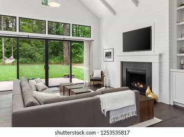 Living Room Interior with Fireplace and Hardwood Floors in New Farmhouse Style Home with Vaulted Ceilings. Shows View of Yard and Trees Through Sliding Glass Doors