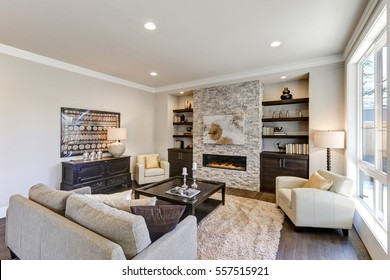 Living room interior in gray and brown colors features gray sofa atop dark hardwood floors facing stone fireplace with built-in shelves. Northwest, USA