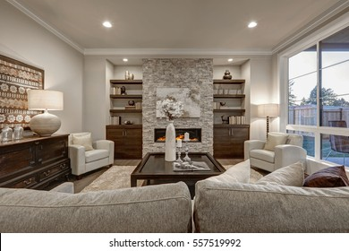 Living room interior in gray and brown colors features stone fireplace with built-in shelves and cabinets, large dark stained cocktail table atop beige fluffy rug and large window.  Northwest, USA