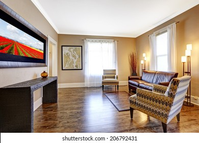 Living room interior with hardwood floor, leather couch and light brown chairs