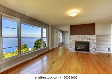 Living room interior with hardwood floor, fireplace with natural stone tile and water view