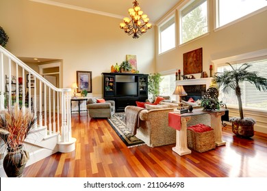Living room interior with high ceiling. Furnished with comfortable sofa, black cabinet with tv, decorated with fake trees