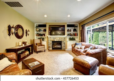 Living room interior with leather furniture set, stone fireplace and tv