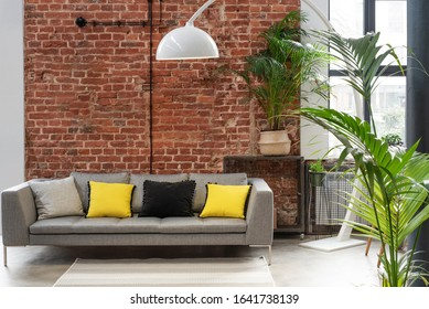 Living room interior in loft apartment in industrial style with brick wall, grey stylish sofa with yellow pillows and big window. Modern lamp and plants in minimal indoors.