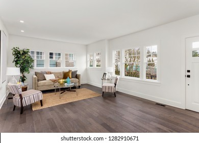 Living Room Interior in New Home with Hardwood Floors, Furniture, and Rug. Features White Walls.