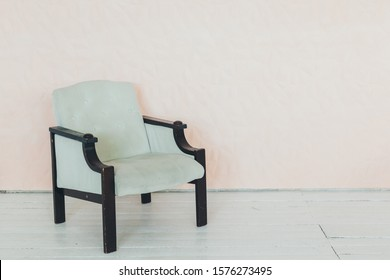 Living room interior wall mock up with pink tufted armchair, pastel pillow, hanging lamp and flowers in vase on empty warm white background.