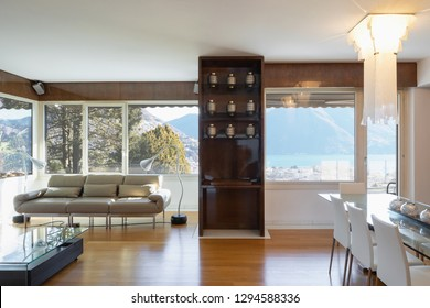 Living room with lacquered wood furniture and lake view window. Nobody inside