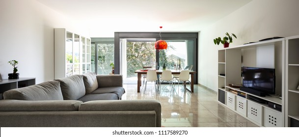 Living room with large designer sofa in modern apartment. Nobody inside