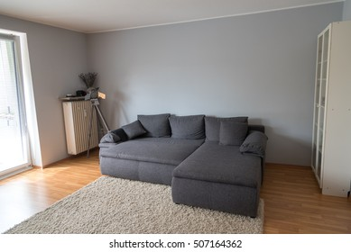 Living room with a large gray sofa bed, a carpet, a lamp and a cabinet