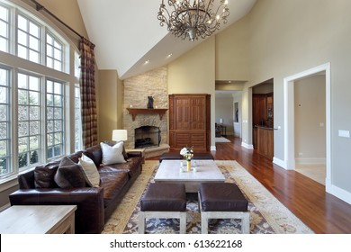 Living room in luxury home with stone fireplace.