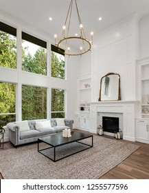 Living Room in Luxury Home with Tall Ceiling, Hardwood Floor, Fireplace, Wall of Windows, and Fireplace