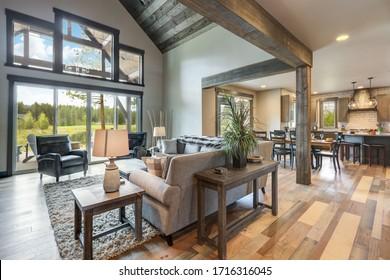 Salon intérieur luxueux avec grande cheminée en pierre et mobilier en cuir et grandes fenêtres aux tons naturels avec télévision.
