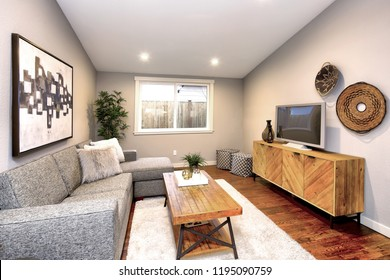 Living room in neutral colors with large gray sofa atop hardwood floor.