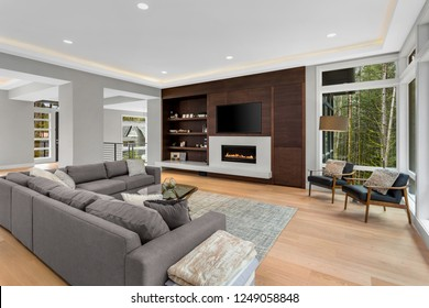 Living room in new contemporary style home, with hardwood floors, fire in fireplace, tv, and large windows