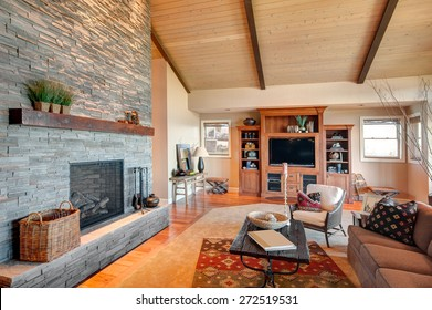 Living Room in New House:Large Furnished Living Room with Fireplace, Vaulted Ceiling, Entertainment Center, Television, Couch, Coffee Table, and Rug