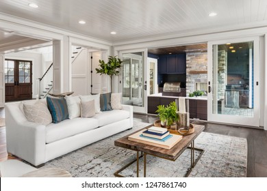Living Room in New Luxury Home with Sliding Glass Doors Leading to Outdoor Covered Patio and Barbecue