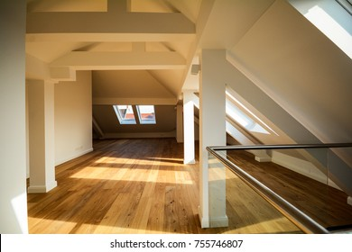 Living room on the rooftop floor, empty apartment with skylight windows and parquet flooring after renovation