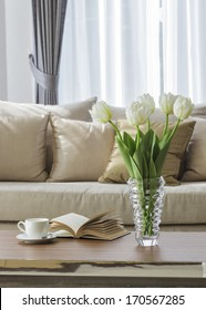 Living room sofa with coffee table book and flower