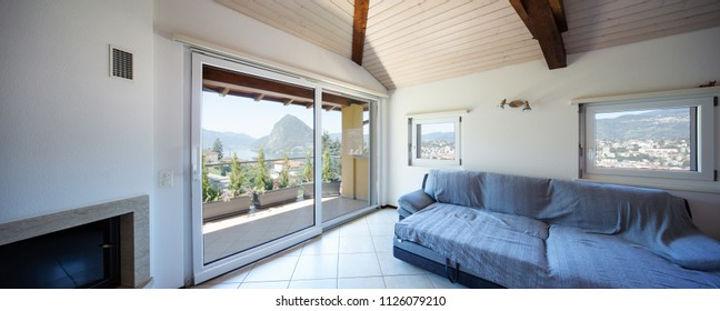 Living room with sofa and large windows overlooking the lake of Lugano and the city