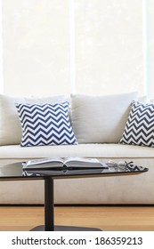 Living room sofa with pillows table book and eyeglass
