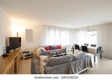 Living room with sofas, table with chairs to eat and a modern kitchen. Interior of open space apartment
