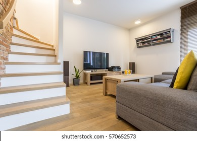 Living room with stairs, sofa and television