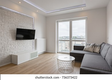 Living room with tv, sofa, balcony and white brick wall