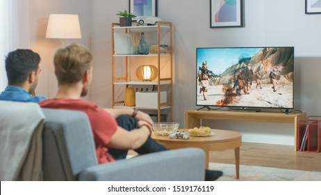 In the Living Room: Two Friends Relaxing on a Couch Watching War Movie on a TV. Modern Military Warfare Action with Shooting and Explosions Shown on a Television.