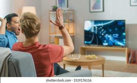 In the Living Room Two Friends Sitting on a Couch Holding Controllers and Doing High Five After Finishing Level in Competitive Video Game, 3D Action Shooter Gameplay Shown on TV Screen.