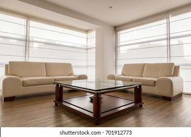 Living room with two large windows, two beige leather sofas, a wooden coffee table with glass top
