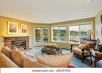 Living room with walkout deck and water front view. Furnished with antique sofa and chair. Gig Harbor.