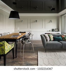 Living room with wooden dining table, couch and black stretch ceiling
