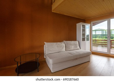 Living room in a wooden organic house. Wooden floor, wooden ceiling. Corky walls. White cupboard. Panoramic windows looking over wooden terrace around the house.