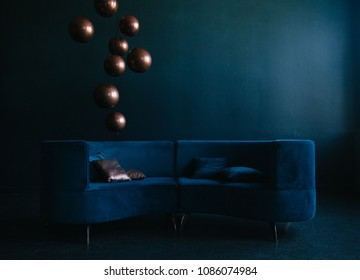 livingroom with blue velvet sofa. golden and blue pillows. sphere bronze lamps. modern interior in blue tones.