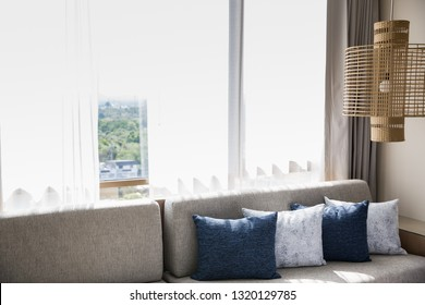 Livingroom Interior with sofa, pillows and vitage lamp near by the window.