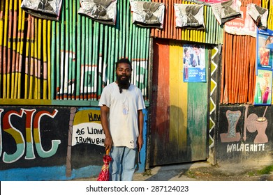 Livingston, Guatemala - March 7, 2015: Garifuna rasta man poses while holding an umbrella in one hand and a machete handle in the other in Livingston, Guatemala. People of Central America