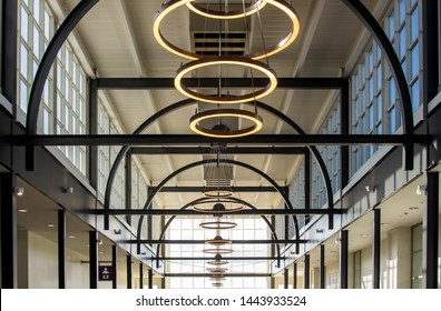 Livingston, Scotland - 21 June 2019: Commercial ceiling in shopping center with round lights in line, arch beam structure and side windows