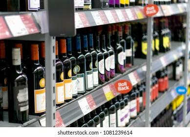 LIVINGSTON, SCOTLAND, UK - APRIL 19, 2018. Asda / Walmart Supermarket. Wine shelf aisle in supermarket with ad on display in foreground.