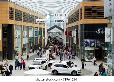 LIVINGSTON, SCOTLAND, UK - AUGUST 18, 2017. Interior of Livingston shopping center. Car showroom display and shoppers, brightly lit