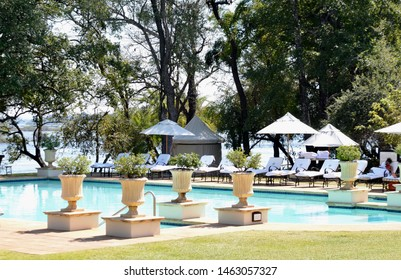 Livingstone, Zambia, Africa. June 2014. A view of the swimming pool at the Royal Livingstone Hotel in Zambia. The Zambezi River can be seen in the background.
